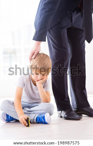 Missing his busy father. Sad little boy holding hand on chin while playing with toy car while his father in formalwear consoling him  - stock photo