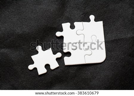 Missing jigsaw puzzle piece white color, business concept for completing the final puzzle piece on black backgorund - stock photo
