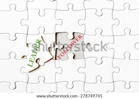 Missing jigsaw puzzle piece with word LEADER, covering text FOLLOWER. Business concept image for completing the final puzzle piece. - stock photo