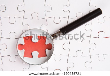 Missing jigsaw puzzle pieces revealing a red surface layer with a magnifying glass - stock photo