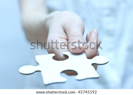 Missing part of puzzle.  Puzzle piece in hand. - stock photo