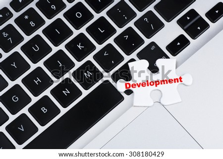 """Missing puzzle with red """"Development"""" text on laptop keyboard as background, business, finance and internet concept - stock photo"""