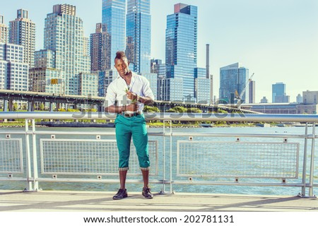 Missing You. Wearing white shirt, green pants, leather shoes, a young black guy with mohawk hair is standing in the front of buildings, holding white rose, looking down, thinking. Urban Casual Fashion - stock photo