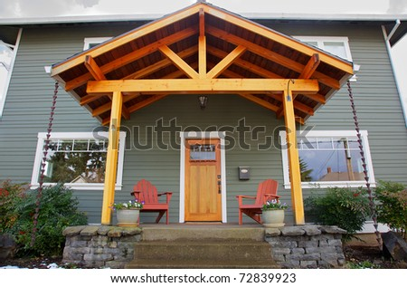 Mission style Stained wood front door with beveled glass surrounded by two Adirondack chairs and flowers - stock photo