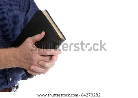 Missionary man holds his bible with interlocked fingers to pray. - stock photo