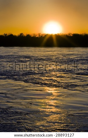 Mississippi river at flood stage with setting sun - stock photo
