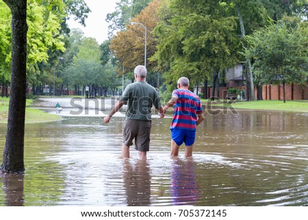 Missouri City, Texas - August 29, 2017: Residents of Sienna Plantation, a Houston suburb walk in high waters. Heavy rains from hurricane Harvey caused floods in many areas around Houston.