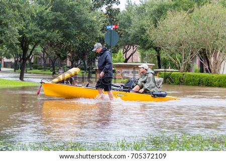 Missouri City, Texas - August 29, 2017: Residents of Sienna Plantation Houston suburb rde a canoe in high waters. Heavy rains from hurricane Harvey caused floods in many areas around Houston.