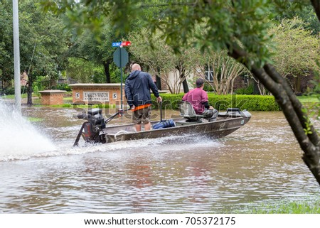 Missouri City, Texas - August 29, 2017: Volunteers from Austin ride a boat in the flooded street, helping local residents to evacuate. Heavy rains from hurricane Harvey caused many floods near Houston