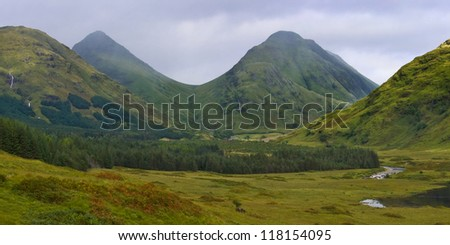 Mist and rain threaten to blow in from a menacing sky over the twin peaks of Stob Dubh and Stob na Broige, deep in the wilderness of beautiful Glen Etive in the Scottish Highlands. - stock photo