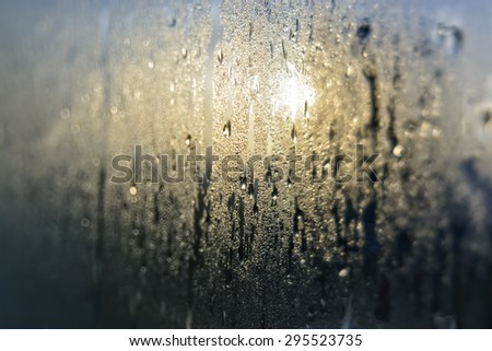 Mist and raindrops on glass pane after a night of rain