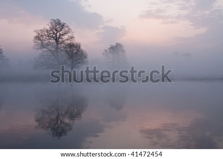 Mist on a lake at dawn with clouds reflected in the calm water - stock photo