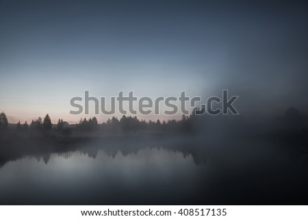 mist over the lake, dusk over the lake, a very dense fog, dawn, blue sky over the lake, the morning comes, the forest reflected in the water, surface water, clear morning sky, gothic   - stock photo
