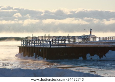 Mist rising from the water and ice  in the harbor. - stock photo