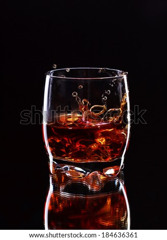 Misted glass of whiskey with splash on dark background, selective focus on the glass - stock photo