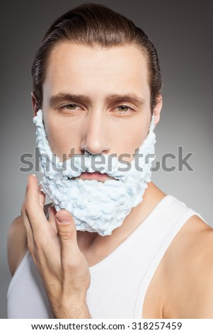 Mister foam beard. The guy is standing and applying shaving foam on his chin. He is looking at the camera seriously. Isolated on grey background