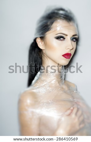 Misterous pretty naked brunette woman wrapped in cellophane looking forward standing on light grey background, vertical picture - stock photo