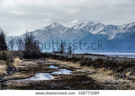 Misty Alaskan Mountains. Train Tracks Following the Turnagain Arm.  From the Seward Highway Near Anchorage, Alaska.  The Great Alaskan Wilderness.  A Beautiful Landscape of Rock, Snow, Water and Ice. - stock photo