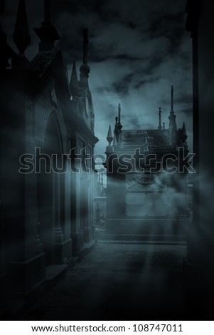 Misty alley of an old European cemetery in blue - stock photo