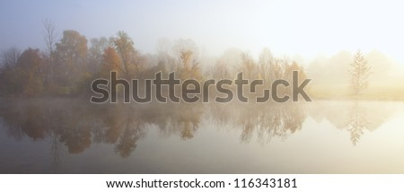 Misty Autumn Morning by Lakeside - stock photo