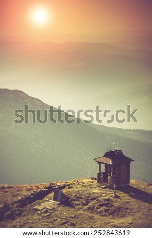 Misty autumn mountain hills landscape. Small chapel with mountains in the background. Fantastic evening glowing by sunlight. Filtered image:cross processed vintage effect.  - stock photo
