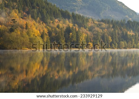 Misty Autumn reflections at Deer Lake, Sasquatch Provincial Park, near Harrison Hot Springs, BC, Canada - stock photo