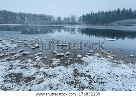 misty clouded winter morning on lake in forest - stock photo