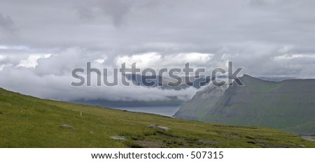 Misty clouds, mountains and water, Faroe Island - stock photo