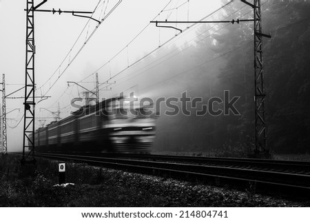 misty country railroad in the early morning with train incoming