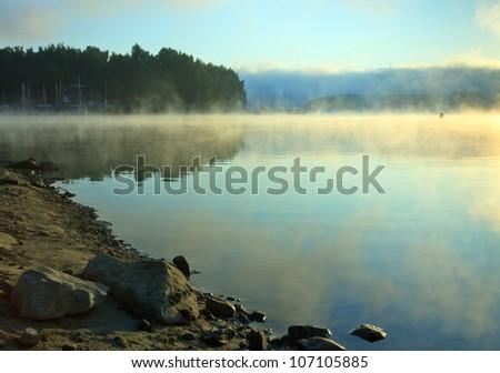 misty dawn at lake - stock photo