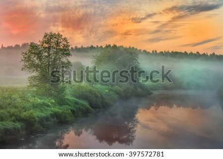 Misty dawn at the river. Beautiful sunrise at the river in the foggy summer morning - stock photo