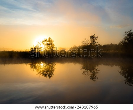 misty dawn over the river. The sun's rays from behind a tree - stock photo