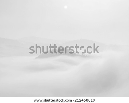 Misty dreamy landscape. Deep misty valley in autumn park full of heavy clouds of dense fog. Sandstone peaks increased from foggy background. Black and white picture.  - stock photo
