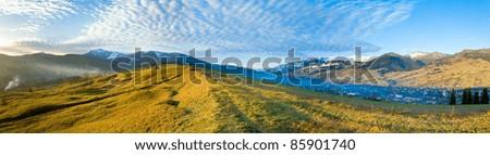 Misty early daybreak in autumn Carpathian mountain, Ukraine (Jasynja Village and Svydovets Range in far). Three shots stitch image. - stock photo
