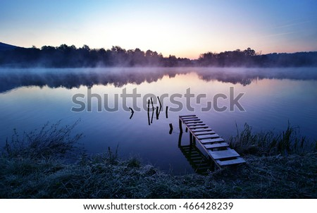 Misty lake in a cold early autumn morning