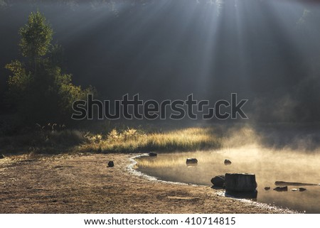 Misty lakeside in morning sunlight and dark background - stock photo