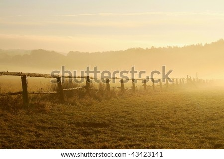 Misty landscape at sunrise with a fence on the pasture of horses. Photo taken in October. - stock photo