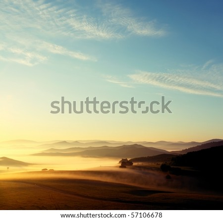 Misty layered mountains in sunrise - stock photo