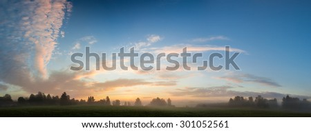 Misty meadow at dawn panorama - stock photo