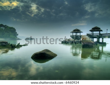 Misty Morning as seen over rocks submerged in tide at pier on beach - stock photo