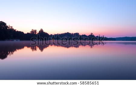 Misty morning at the lake with houses - stock photo
