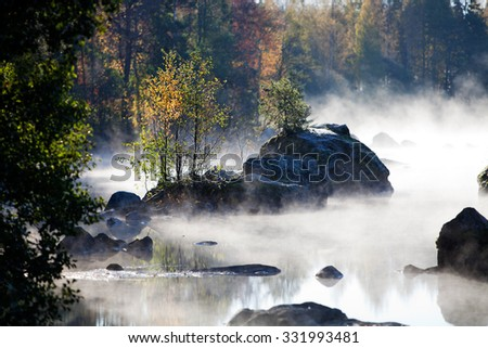 Misty morning by the lake in autumn - stock photo