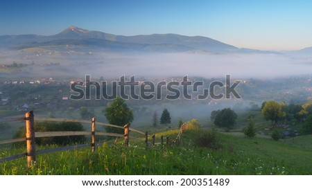 Misty morning in the mountains. View of the village under the fog. Wooden fence on a green meadow. Carpathian mountains, Ukraine, Europe - stock photo