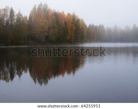 Misty morning on lake in Finland with beautiful colored trees in Autumn