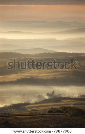 misty morning over a small village - stock photo