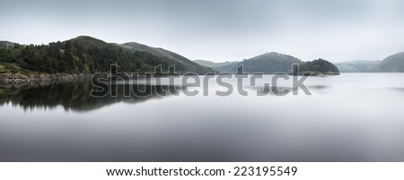 Misty morning panorama landscape over calm lake in Autumn - stock photo