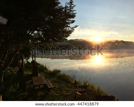 Misty morning sunrise. The early morning sun rising over a misty lake in the summer. Summer time camping at the lake. Bright orange sun on a calm lake in the early morning. - stock photo