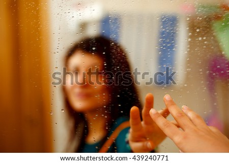 misty reflection of girl in the mirror with water droplets - stock photo