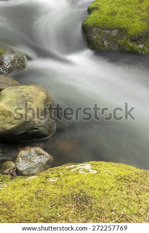Misty roaring waterfall cascading down through the forest - stock photo