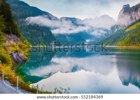 Misty summer morning on the Vorderer Gosausee lake with view of Dachstein glacier. Colorful outdoor scene in Austrian Alps, Salzkammergut resort area in the Gosau Valley in Upper Austria, Europe.